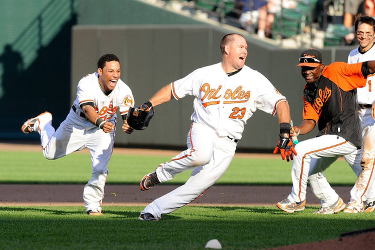 Ty Wigginton #23 of the Baltimore Orioles is chased by Robert Andino #12 after driving in the game winning run in the eleventh inning against the New York Yankees. (Photo by Greg Fiume/Getty Images)