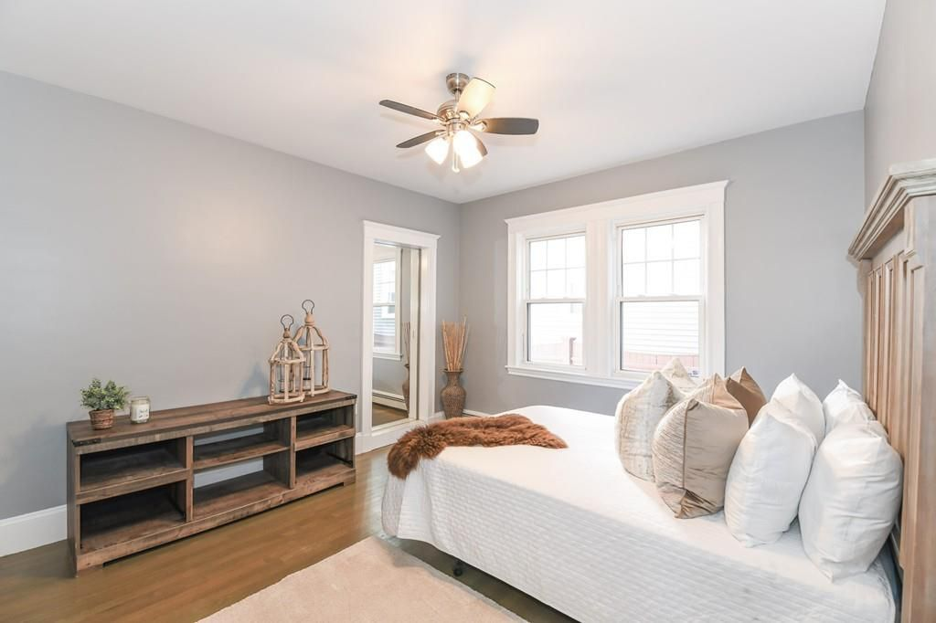 A bedroom with a bed and some low shelves facing the bed.