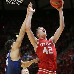 Utah Utes forward Jakob Poeltl (42) puts in a shot over Brigham Young Cougars center Corbin Kaufusi (44) as Utah and BYU play in the Huntsman Center in Salt Lake City Wednesday, Dec. 2, 2015. Utah won 83-75.