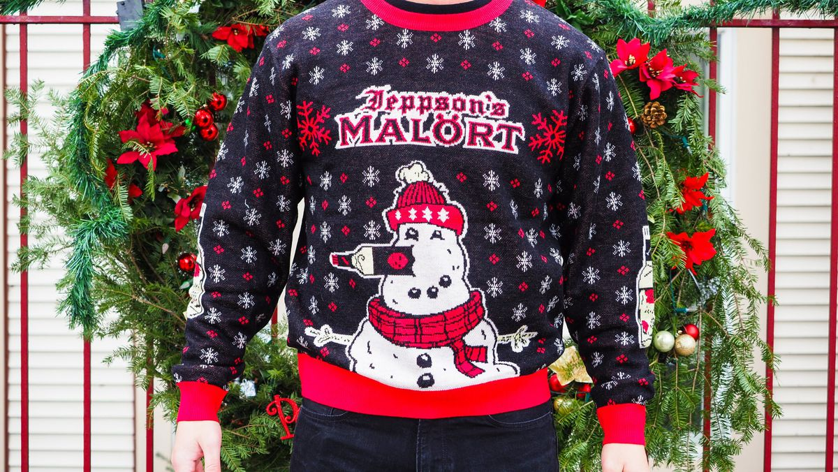 A person wearing a very ugly Malort-themed Christmas sweater.