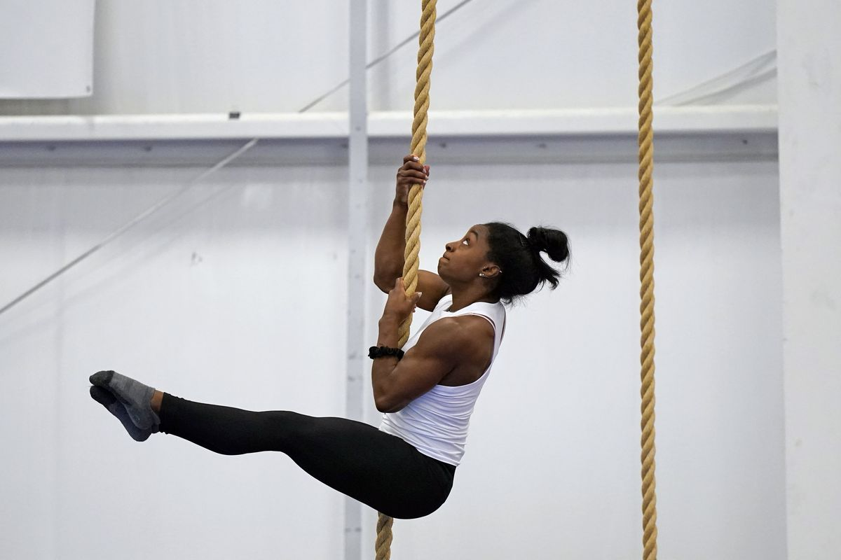 Olympic champion gymnast Simone Biles climbs a rope during a training session.