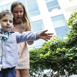 Dash Johnson, 4, left, a patient at Primary Children's Hospital, and his sister, Aspen Johnson, throw money into a pond during the reopening of the Angel Garden at the hospital in Salt Lake City on Monday, Aug. 1, 2016. The redesigned garden includes more than 1,000 new plants and trees, as well as legacy monuments, including the Butterfly Angel statue, a commissioned 5-foot bronze. Dash's family spearheaded renewal project.