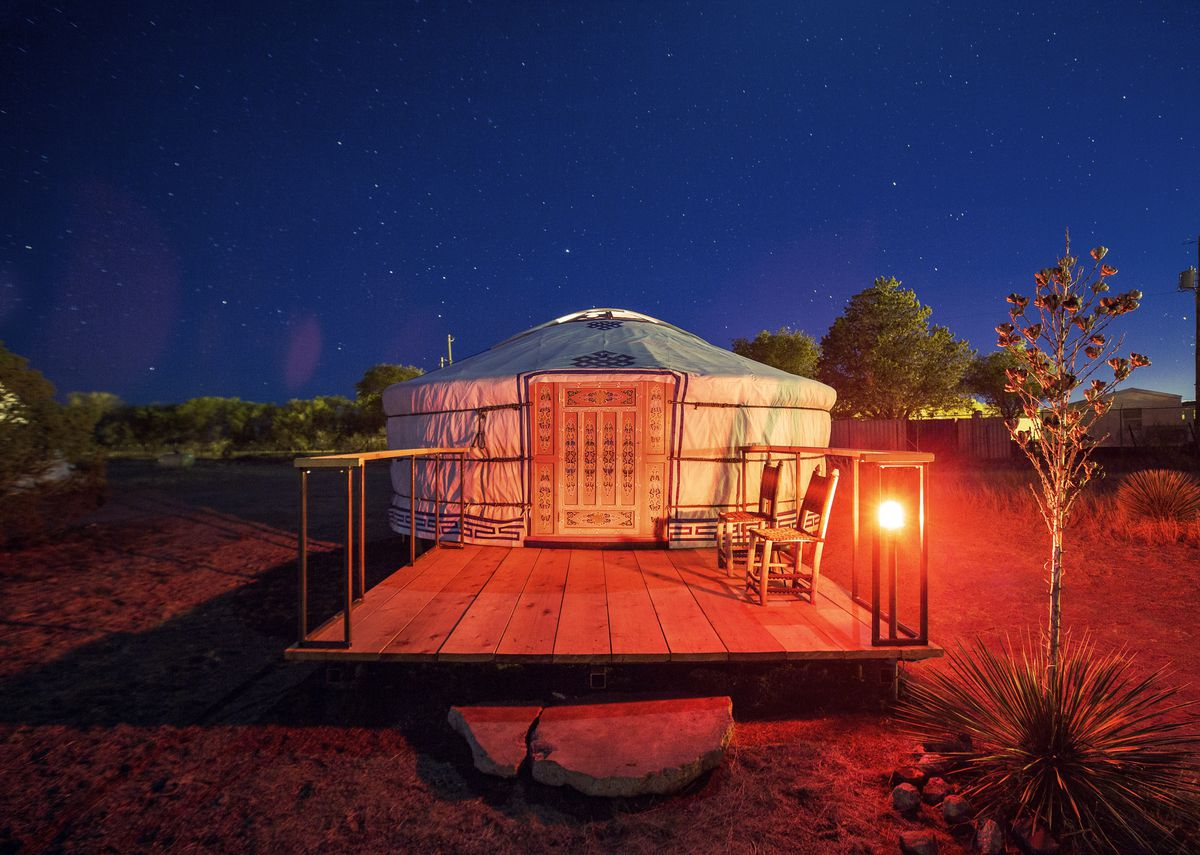 The exterior of a yurt in Texas. The facade is tan with a wooden deck. The yurt is surrounded by trees.