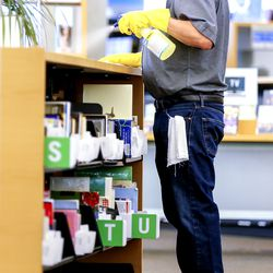 Bruce Jensen, a part-time custodian, cleans surfaces at the Main Library in Salt Lake City on Monday, Sept. 21, 2020. All branches of the Salt Lake City Public Library reopened Monday for express services, which include 30-minute computer sessions, access to fax/copy machines, holds pickup, item return and reference assistance.