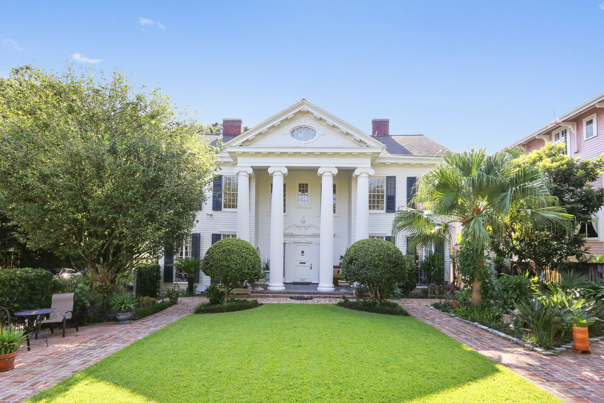 A white mansion with four huge columns on a big green lawn