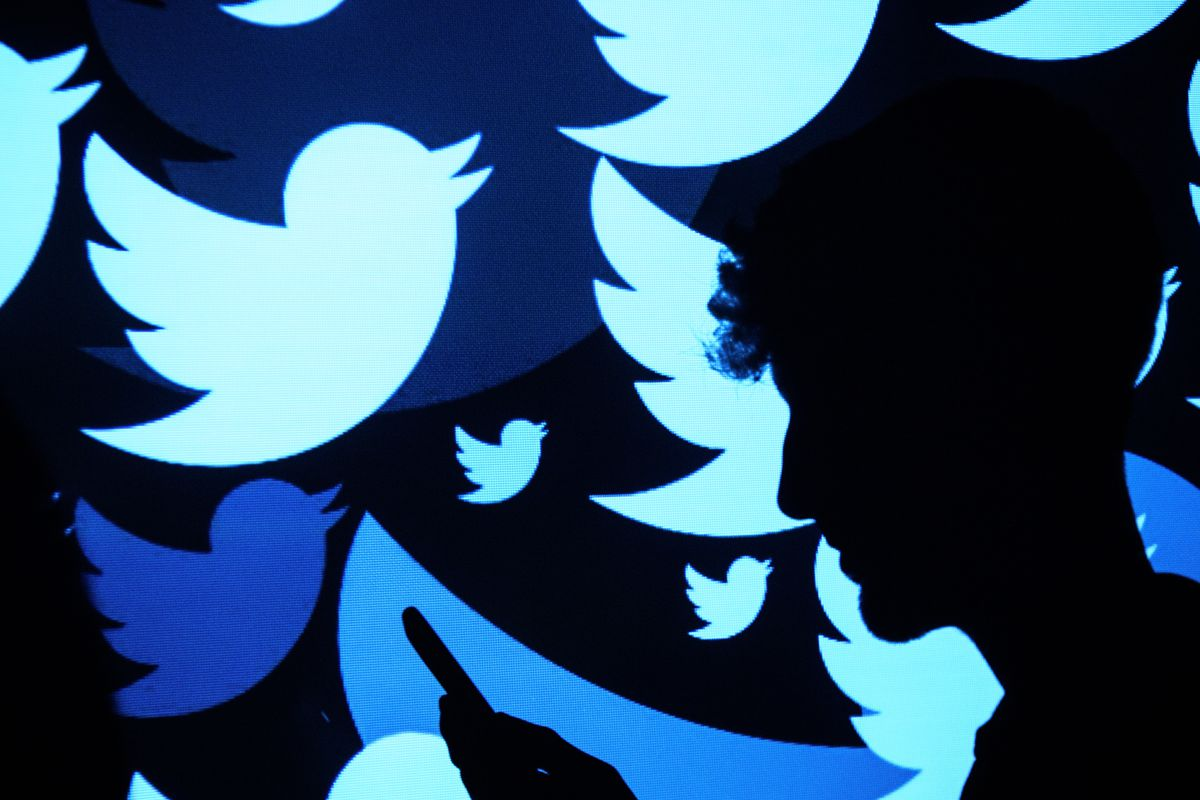 A silhouette of a man in front of several Twitter bird logos