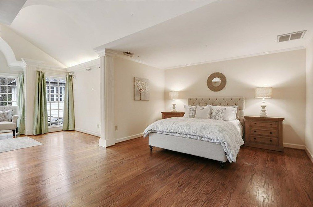 A big master bedroom with a barrel ceiling and sitting room at left.