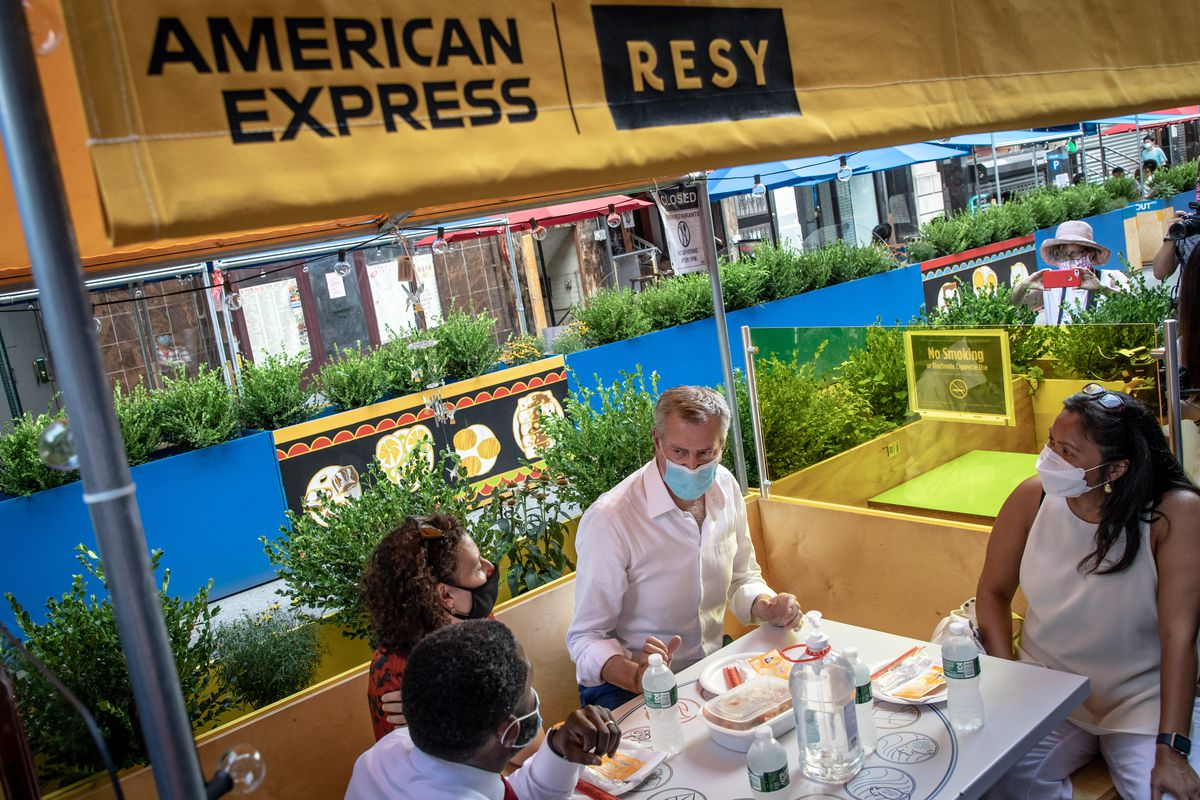 Mayor Bill de Blasio sitting and eating food with other people under a tent