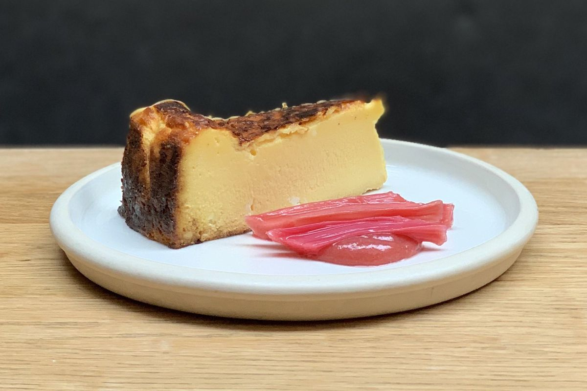 A slice of Basque cheesecake, served on a white deep ceramic plate, with poached rhubarb