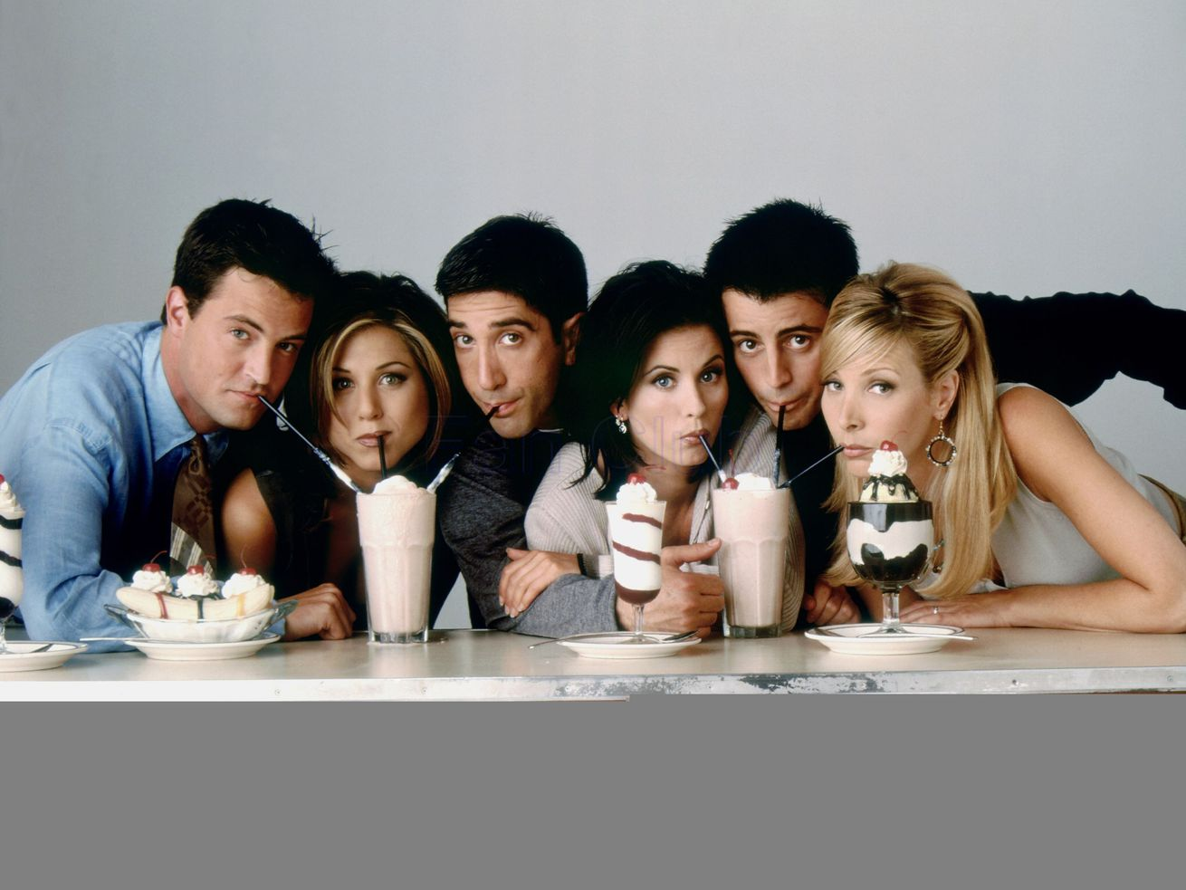 """The cast of """"Friends"""" leaning forward and sipping on milkshakes sitting on a table."""