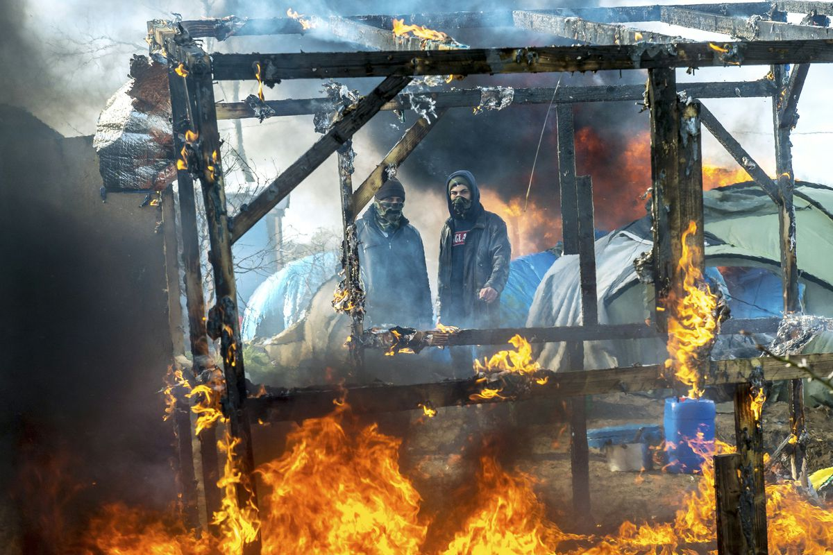 """A makeshift shelter in the Calais refugee camp known as """"the Jungle"""" burns as French police dismantle a section of the camp."""