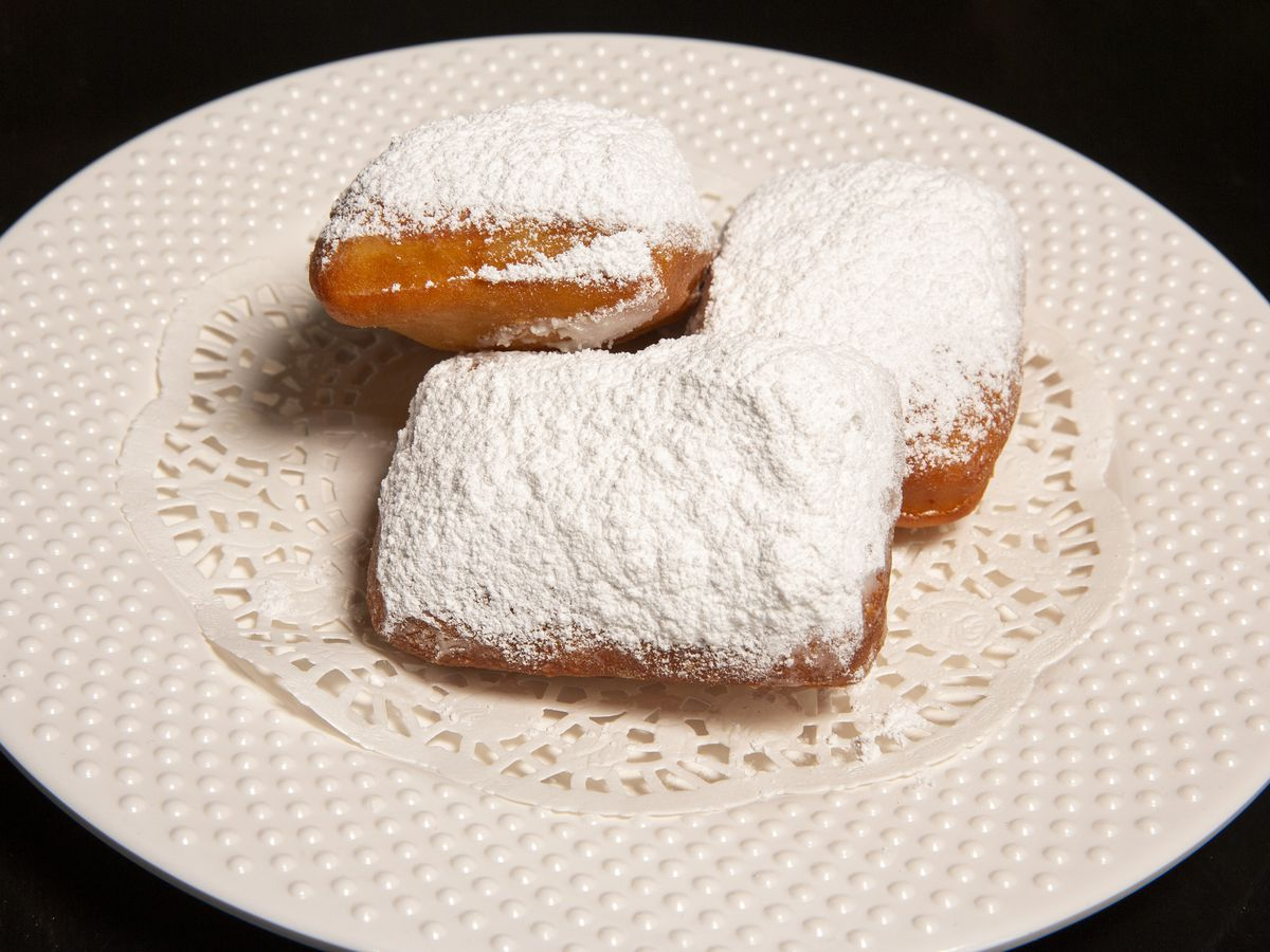 A round white plate that holds three beignets covered in powered sugar.