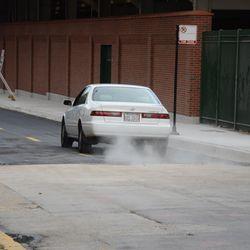 Mon 5:16 p.m. Car kicking up dust, at the gap where the asphalt surface begins -