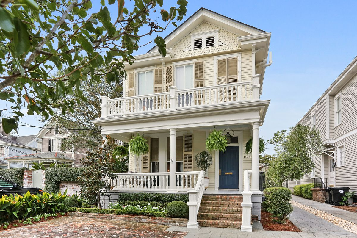 A two story victorian home with balcony sits behind a large tree