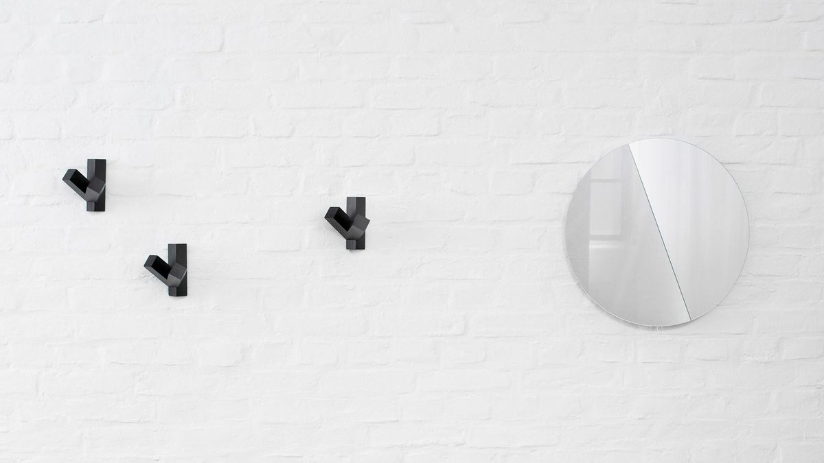 White brick wall with round, bisected mirror mounted on it along with three black coat hooks.