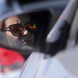 Damelis Carmona waits in her car to pick up food from the Utah Food Bank in the parking lot of a chapel belonging to The Church of Jesus Christ of Latter-day Saints in Taylorsville on Monday, April 13, 2020. The Utah Food Bank estimates it provided food to around 400 families at this location.