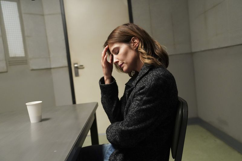 "Actress Cobie Smulders as Dex Parios in ""Stumptown"" sits in a police witness interview room by herself with her eyes closed and puts her hand to her head."