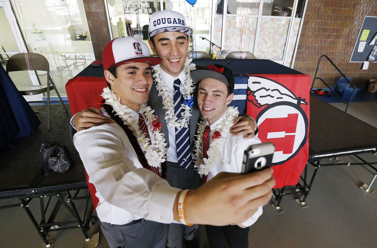 Timpview football players, left to right, Gabe Reid, Devin Kaufusi and Britain Covey take a photo as they sign their Letters of Intent in Provo Wednesday, Feb. 4, 2015.