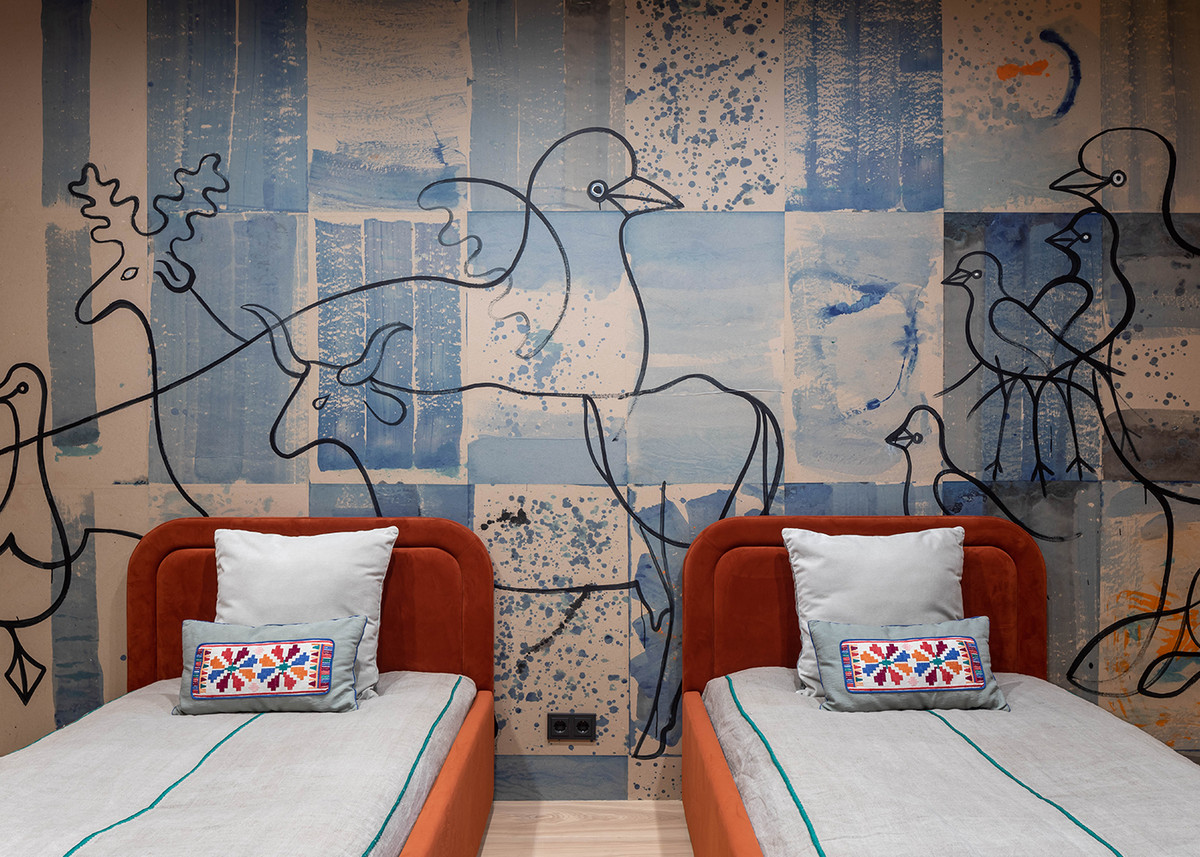 A children's bedroom with small red and orange beds and blue and white wallpaper with animals printed.