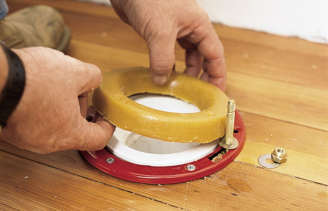 Man Placing Wax Ring Over Flange For Toilet Installation