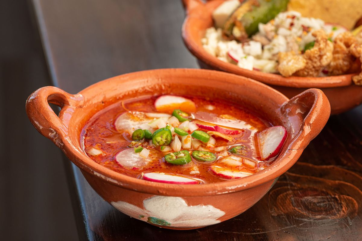 Red pozole with toppings to the side
