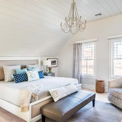 """New windows made in the Queen Anne style and pale finishes throughout bring an airy serenity to the main bedroom, accentuated by the raised ceiling. Gold notes in the chandelier are repeated in the furnishings. <em>New windows: </em><a class=""""ql-link"""" href=""""https://www.marvin.com/"""" target=""""_blank""""><em>Marvin</em></a><em>; Chandelier: </em><a class=""""ql-link"""" href=""""http://generationlighting.com/"""" target=""""_blank""""><em>Generation Lighting</em></a>"""