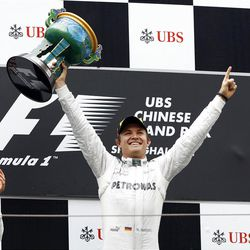 Mercedes Formula One driver Nico Rosberg of Germany, center, celebrates after winning the Chinese Grand Prix.  in Shanghai, Sunday, April 15, 2012. McLaren driver Jenson Button of Britain, who finished second, is at left, and his third placed team mate Lewis Hamilton of Britain is at right.   (AP Photo/Eugene Hoshiko)in Shanghai, Sunday, April 15, 2012. McLaren driver Jenson Button of Britain, who finished second, is at left, and his third placed team mate Lewis Hamilton of Britain is at right.   (AP Photo/Eugene Hoshiko)
