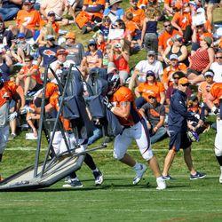 Broncos rookie T Austin Fleer helps move the 2-man sled.