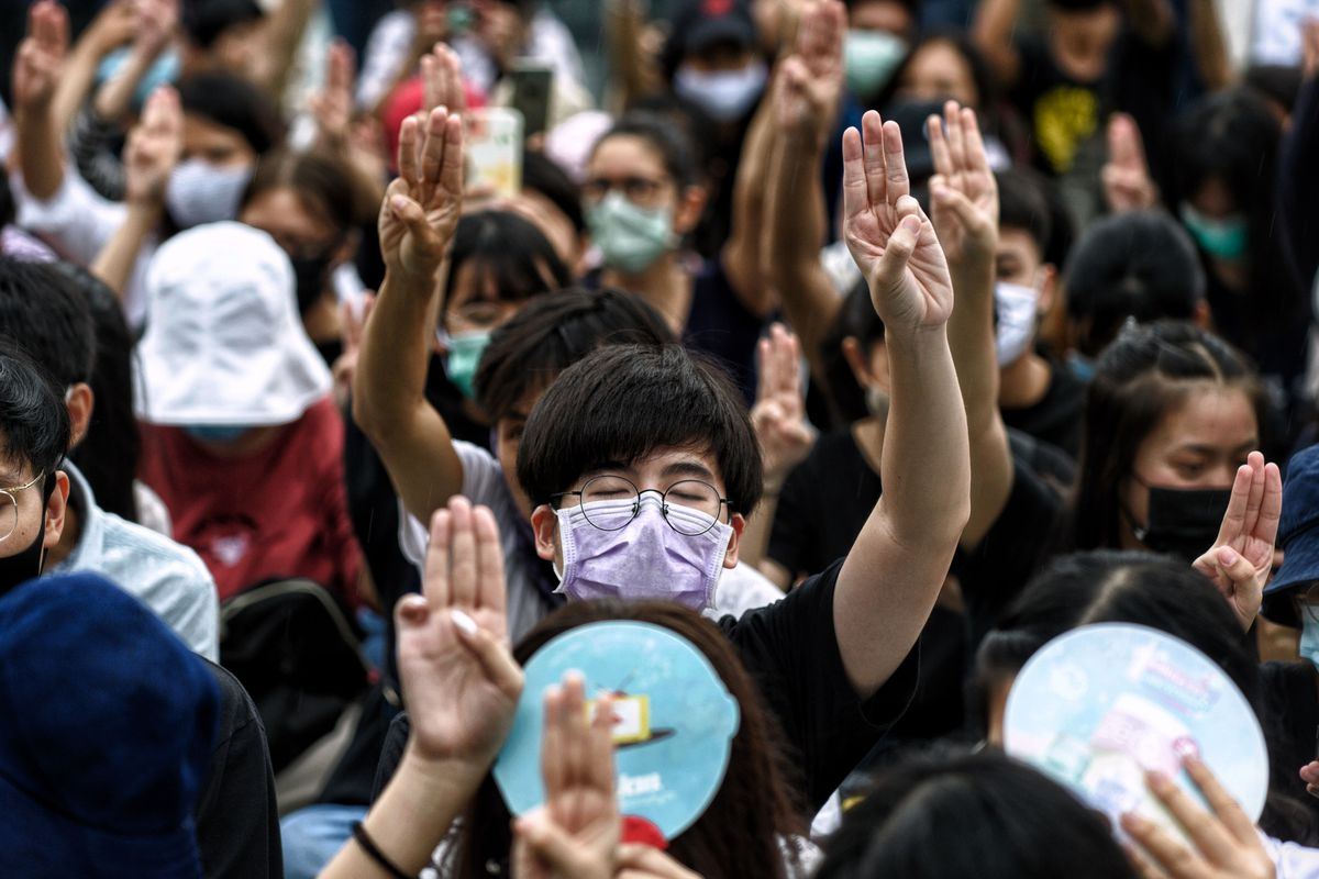 A mass of masked protesters raise their arms, their hands in a three-fingered salute. In the center of the photo is a young man with black rimmed glasses, wearing a purple mask.