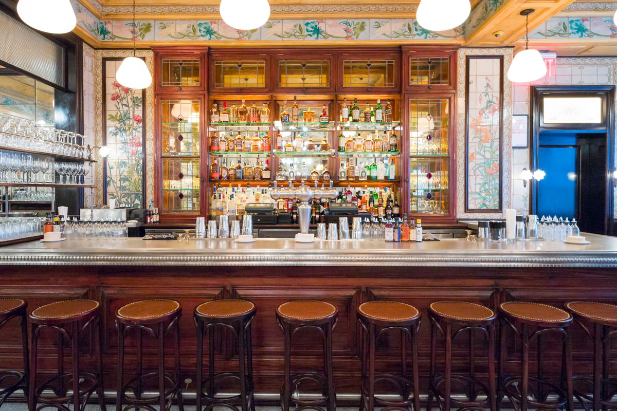 Brown barstools stand against a long wooden bar, where four rows of alcohol bottles are backlit