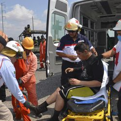 First responders treat a man after an explosion ripped through a gas pipeline distribution center in Reynosa, Mexico near Mexico's border with the United States, Tuesday Sept. 18, 2012. Mexico's state-owned oil company, Petroleos Mexicanos, also known as Pemex said the fire had been extinguished and the pipeline had been shut off but ten people were killed during the incident.