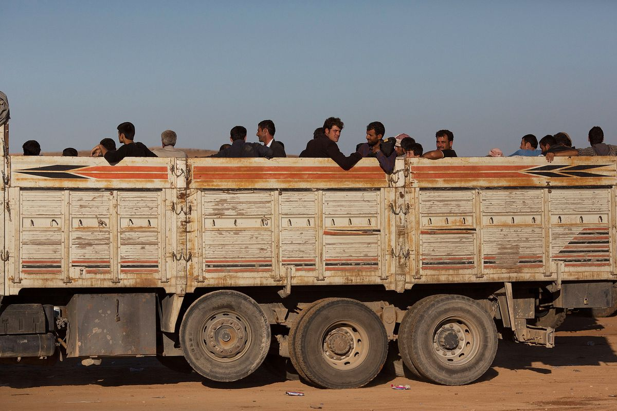 Refugees ride in the back of a truck after crossing the border from Syria into Turkey