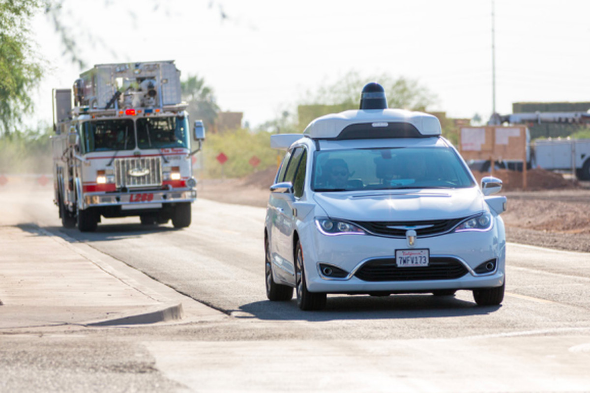 Waymo's self-driving car driving ahead of a fire truck.