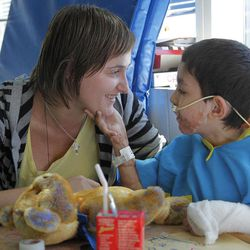 In this Wednesday, Aug. 29, 2012 photo, Ihor Lakatosh, of Ukraine, right, who is eight or nine years old, and weighs less than 30 pounds, interacts with his legal guardian Anna Rishko, also of Ukraine, left, in his room at Shriners Hospital for Children, in Boston. Lakatosh, who has burns on over 30 percent of his body, was brought to Shriners through a non-profit organization, and may walk again after multiple surgeries and extensive physical therapy.