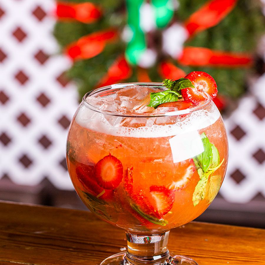 A large colorful cocktail in a goblet with a wreath behind it.