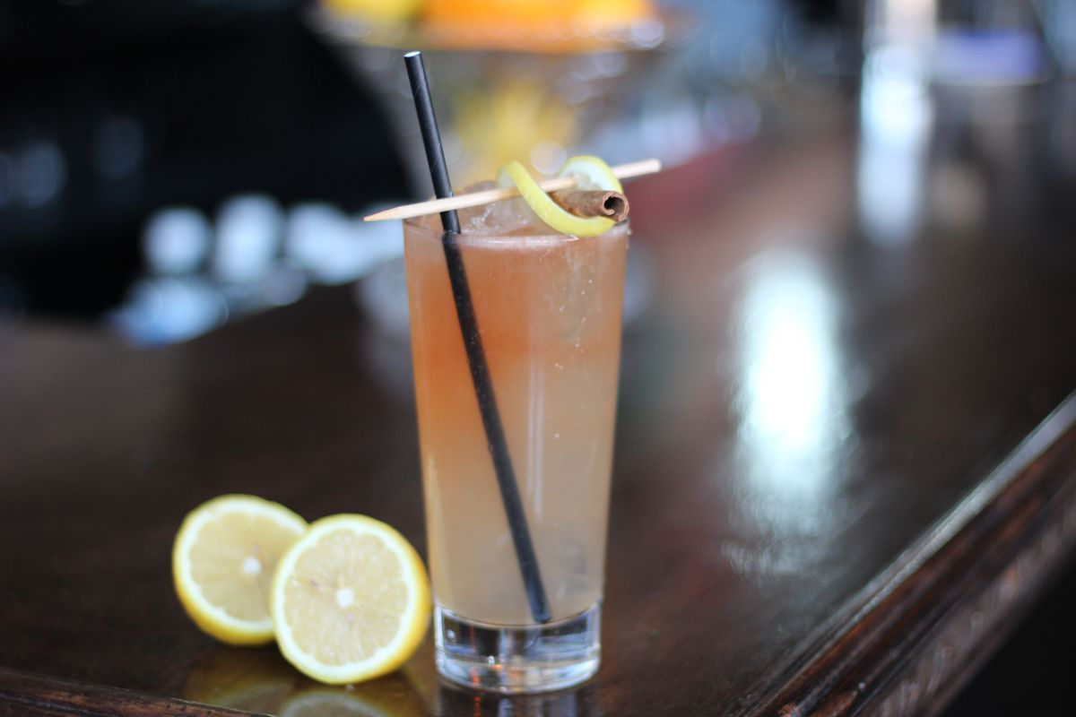 A cocktail filled in a tall glass with sliced lemon.