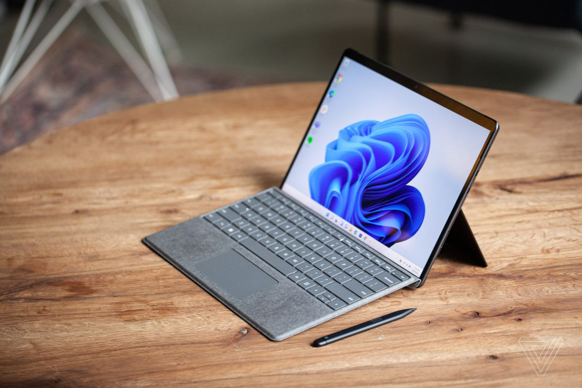 The Surface Pro 8 seen from above and to the right on a table with the Surface Slim Pen 2 next to it and Signature Keyboard attached. The screen displays a blue swirl on a white background.