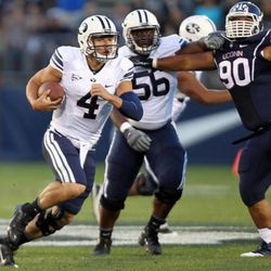 BYU quarterback Taysom Hill (4) runs past BYU offensive lineman Tejan Koroma (56) and Connecticut Huskies defensive tackle Julian Campenni (90) during a football game at Rentschler Field in East Hartford, Conn., on Friday, Aug. 29, 2014.