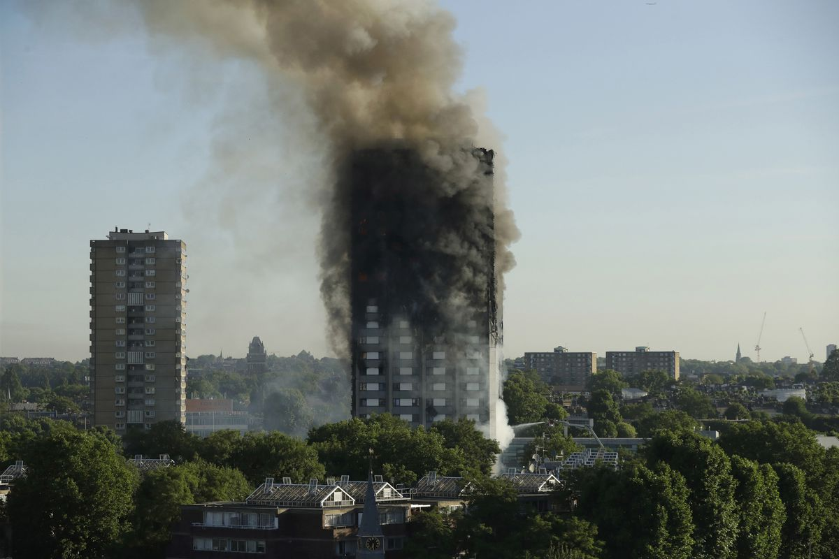 FILE- In this June 14, 2017, file photo, smoke rises from a high-rise apartment building on fire in London. Six months after flames enveloped the high-rise in London and prompted concerns about the safety of other buildings worldwide, a U.S.-based fire pr