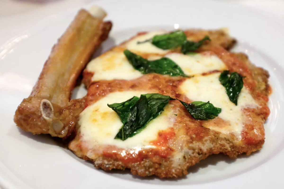 a white plate of veal parmesan covered in red tomato sauce, gooey white cheese and basil leaves. next to the veal is a bone of some sort.