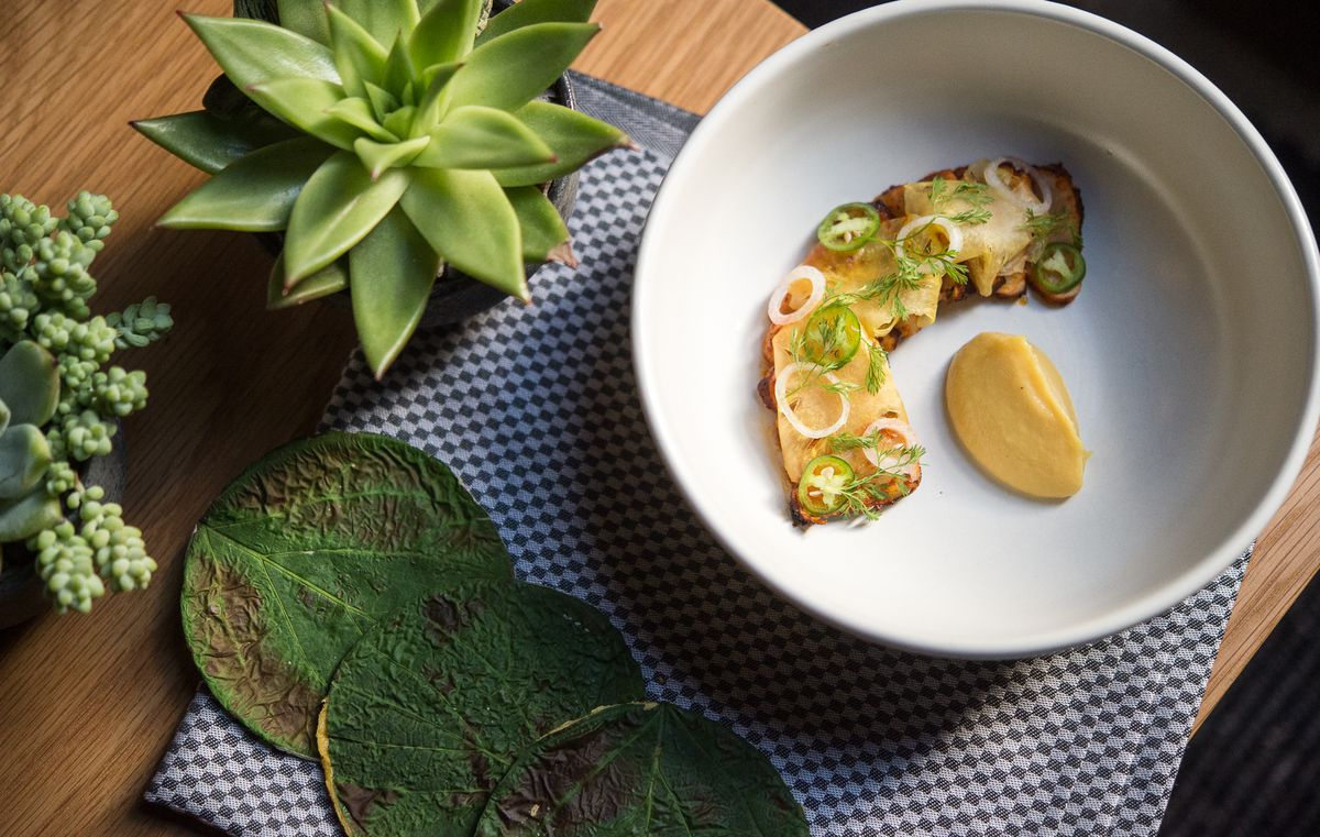 A half-moon of grilled cobia sits at the bottom of a shallow bowl, with a puree of pineapple sitting to its right