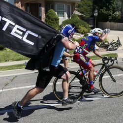 """""""Fireman"""" Rob Verhelst runs alongside a rider dropped by the peloton on the Eagle Ridge Drive climb during Stage 3 of the Tour of Utah in North Salt Lake on Thursday, Aug. 15, 2019."""