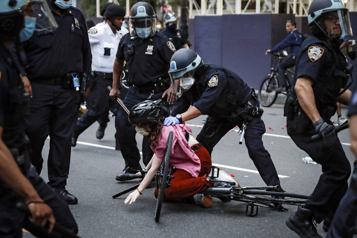 In this June 3, 2020 file photo, a protester is arrested by NYPD officers for violating curfew beside New York's iconic Plaza Hotel, following the death of George Floyd, who died after being restrained by Minneapolis police officers.