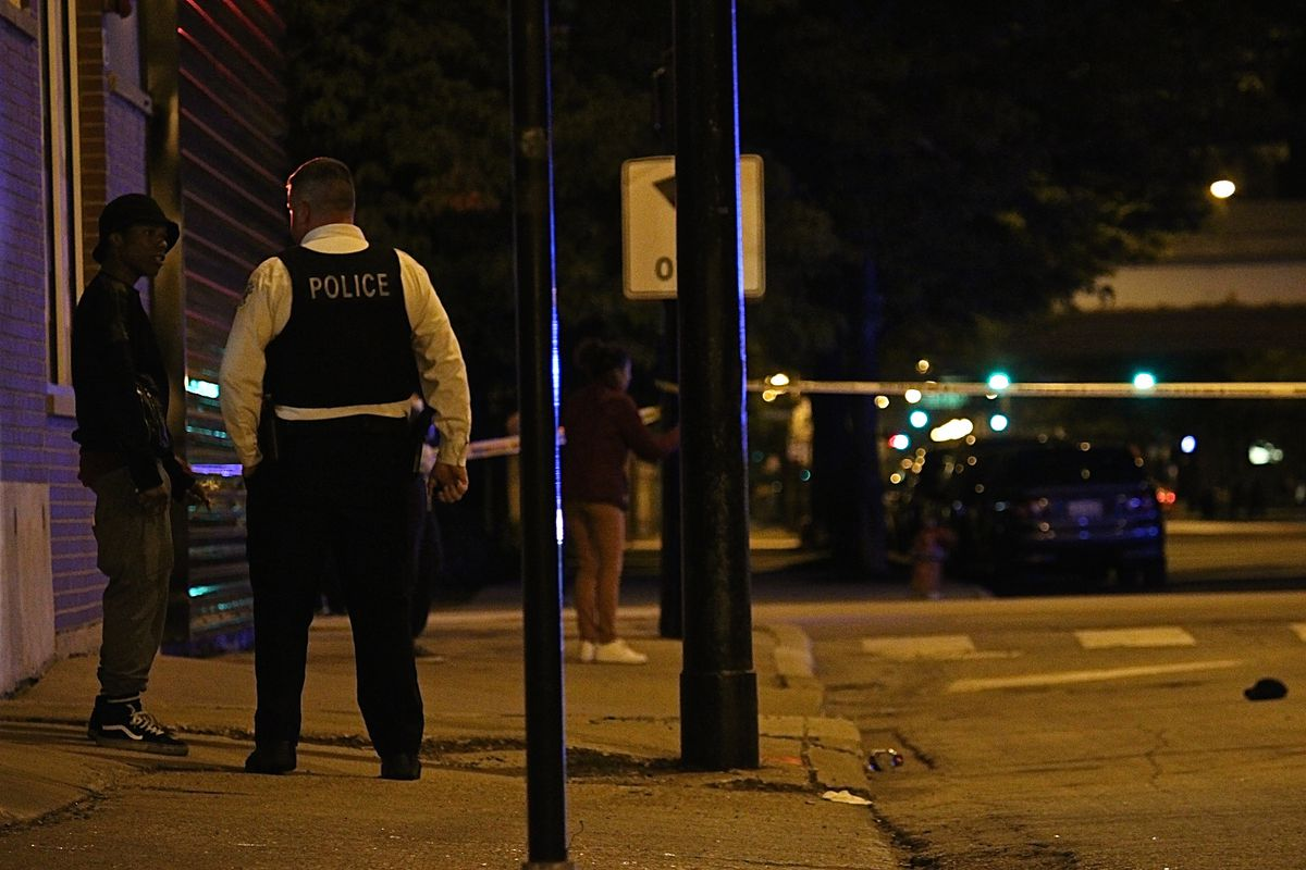 A witness speaks to a police officer at the scene of a shooting in the South Loop early Thursday. | Daniel Brown/Sun-Times