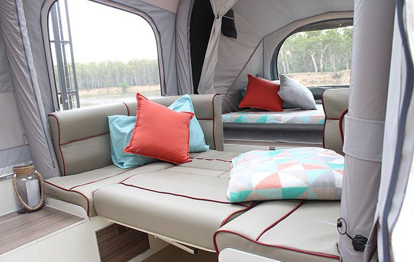 The interior of a camper trailer. There are grey cushions in a pullout bed. There are pillows and blankets. The walls are light grey tent material.