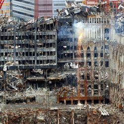 ** HOLD FOR WEEKEND STORY BY DAVID CARUSO ** In this file photo of Dec. 11, 2001 sparks cascade from the remains of the World Trade Center as dismantling continues in the pit at ground zero. While Americans grieved the 9/11 attacks and U.S. troops went to war in Afghanistan, another army, one made up of ironworkers, heavy equipment operators and mason tenders, battled day and night to clear away the destruction in Lower Manhattan and recover the bodies of the dead. (AP Photo/ Louis Lanzano, File)
