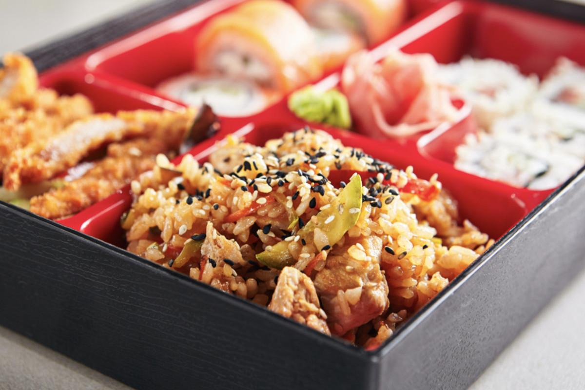 A closeup view of a bento box with rice, sushi, and tempura.