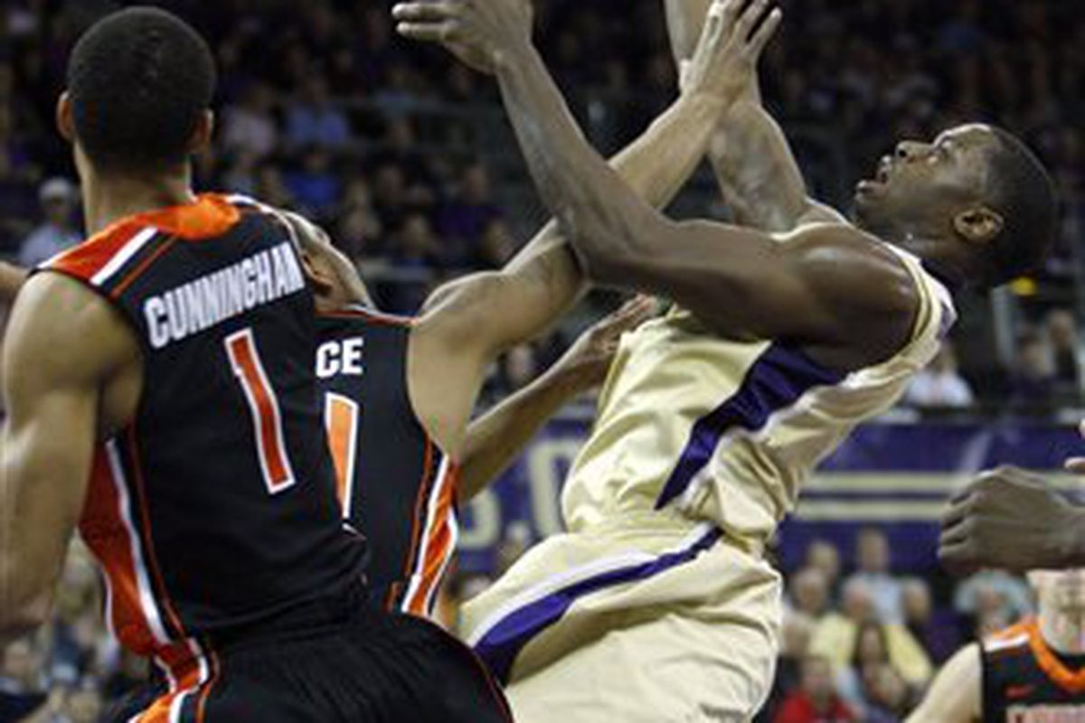 Oregon State's Jared Cunningham and Lathan Wallace try to defend Washington's Matthew Bryan-Amaning, who led the Huskies with 24 points and 15 rebounds.  <em>(AP Photo/Kevin P. Casey)</em>