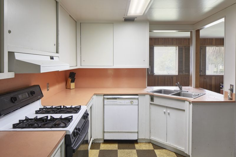 Kitchen with white cabinets, white appliances, and coral countertops.