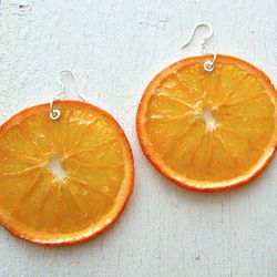 """Actual orange slices lend their beauty to these <a href=""""http://www.etsy.com/listing/95707241/real-orange-slice-earrings-fruit-jewelry?"""">Preserved Orange Earrings</a> ($28) by Philly artist Zoe Einbinder."""